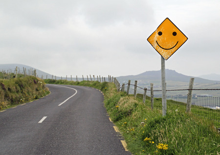 Yellow road sign with smiley ahead of a curve in a hilly landscape