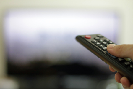 hand with remote control and TV set in the background