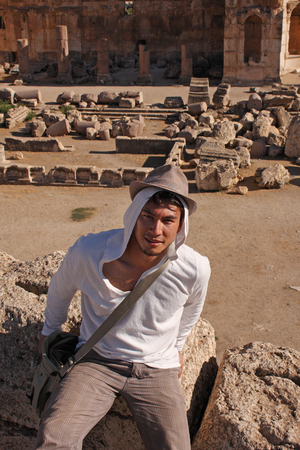 Young man with a hat sitting on ancient Roman ruins in Lebanon