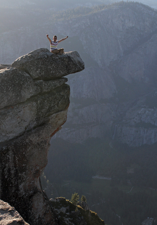 Young man raises his arms at the edge of steep cliffs in Yosemite national park