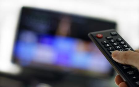 Hand mit Fernbedienung: Binge-Watching-TV-Show
