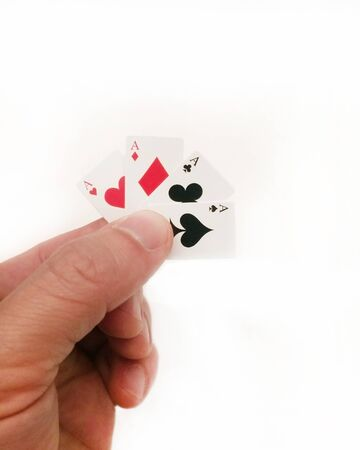 Hand holding tiny cards: Four Aces