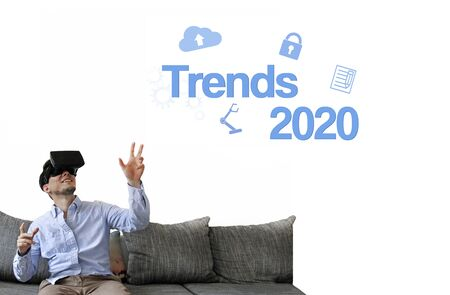 Man with VR goggles on couch gesturing towards IT & technology trends