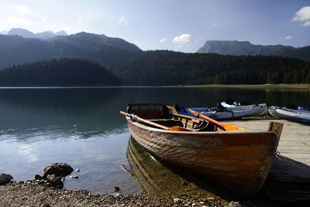 Rowing boats and canoes at a pier at the Black Lake, Montenegro Stock fotó