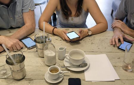 Planning  session: People in cafe all using their smartphones at the table Stockfoto