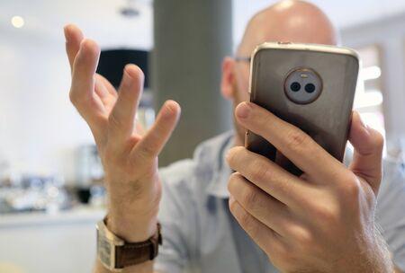 Man gesturing vividly while handling smartphone Stockfoto
