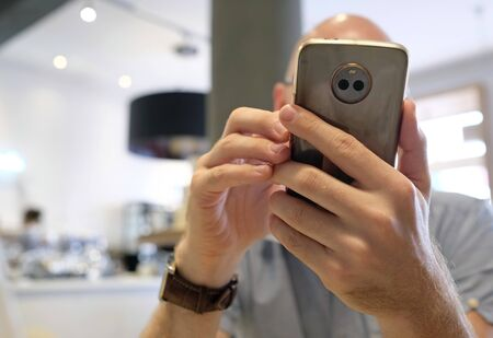 Man handling smartphone in a cafe Stockfoto