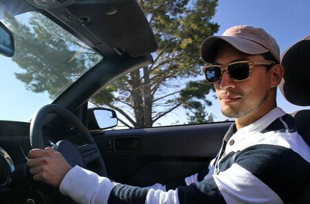 Young man with wooden sunglasses and baseball cap driving a convertible