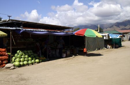 Market stall in Cholpon Ata protected by the midday sun, with mountains in the background