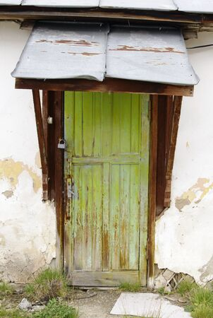 Weathered green wooden door with a small metal roof