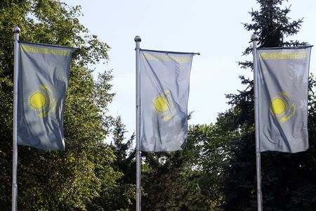 Three national flags of Kazakhstan on flag poles in the city of Almaty on a sunny day