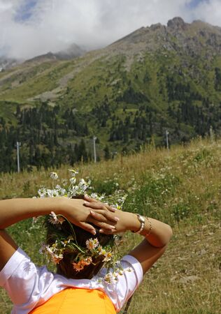 Relaxed woman with flowers in her hair in the mountains near Almaty, Kazakhstan