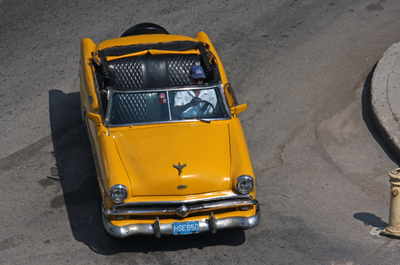 Havana, Cuba - June 29, 2019: Aerial view of a yellow classic car turning left in the city of Havana, Cuba.