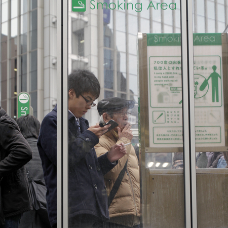 Tokyo, Japan - May 15, 2019: Smokers standing in a designated smoking area in the city.