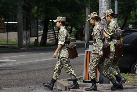 Almaty, Kazakhstan - August 24, 2019: Three women in uniform crossing a street in Almaty. Sajtókép