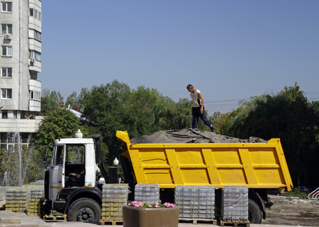 Almaty, Kazakhstan - August 23, 2019: Worker on top of a truck at construction site in Almaty, Kazakhstan. Sajtókép