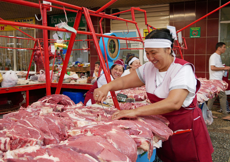 Almaty, Kazakhstan - August 24, 2019: Smiling female working in the meat section of the famous Green Bazaar in Almaty, Kazakhstan