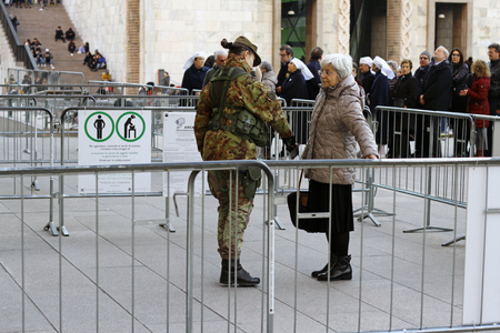 Milan, Italy - December 14, 2018: A senior woman is frisked by a soldier wearing a camouflage uniform before entering the cathedral in Milan. Sajtókép
