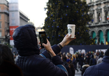 Milan, Italy - December 14, 2018: A young man holds up a Starbucks paper cup and takes a photo of it with his mobile phone. Sajtókép