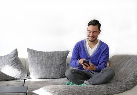 Smiling man using smartphone while sitting on the couch Stock fotó