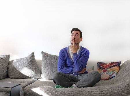 Man on couch contemplating options with a finger touching his lips