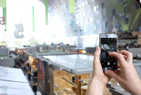 Person taking a photo of a big mall with his smartphone Stock fotó