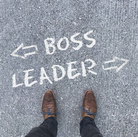 A man in leather shoes stands in front of the words Boss and Leader with arrows pointing left and right