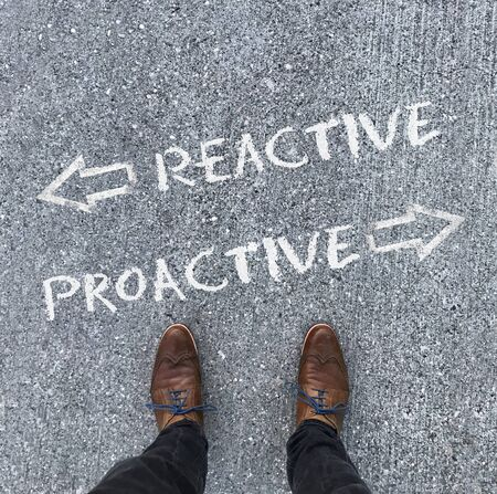 A man in leather shoes stands in front of the words Reactive and Proative with arrows pointing left and right