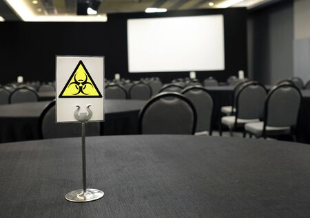 Coronavirus and cancellations: Empty conference center and bio hazard sign