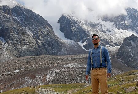 Man with aviator sunglasses in front of a mountain panorama