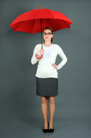 protecting spectacles: businesswoman with red umbrella