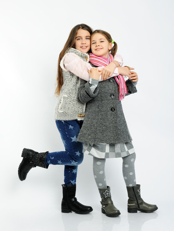 children clothing: cheerful girls in a winter clothes