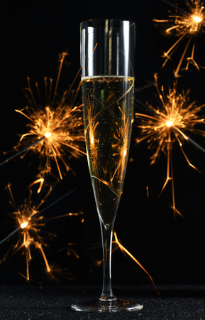 glass with champagne and sparkles