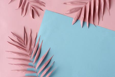 arrangement van roze palmbladeren en gekleurd papier