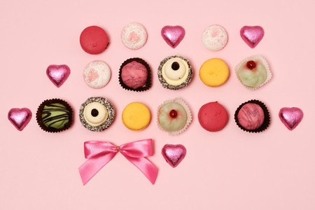 arrangement of mini cakes and macaroons on a pink background