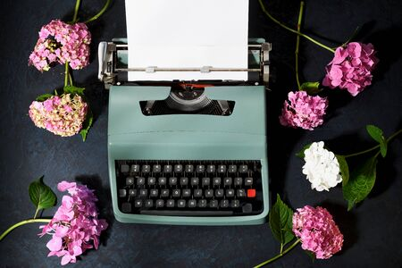 vintage typewriter with hydrangea flowers, overhead view