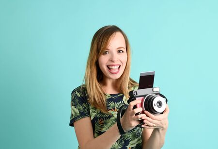 Pretty young woman with instant camera on a green background