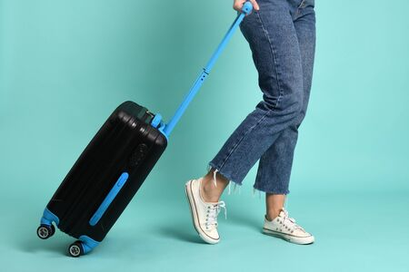 Young woman with luggage on a green background