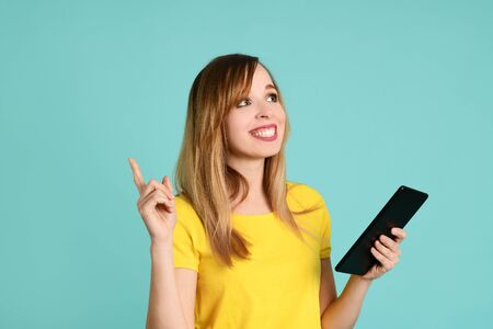 Pretty excited woman with tablet on light green background 版權商用圖片