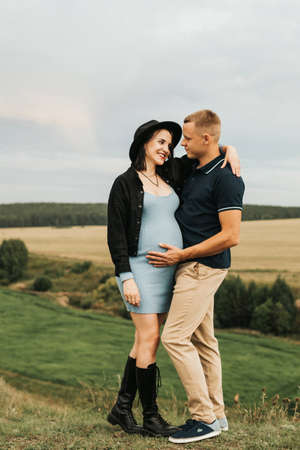 Beautiful pregnant woman and her husband. A couple of happy people. High quality photo