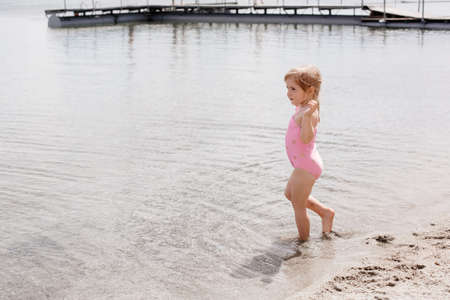 Photo of a little girl running along the sandy shore of the lake against the backdrop of the water. Rest on the shore. Three year old girl on the coast. High quality photo