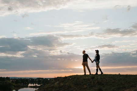 Silhouette of a couple of people on a sunset background. A pregnant woman and her husband are walking in the evening. selective focus. High quality photo