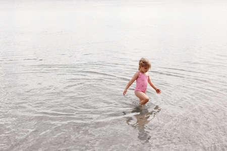 跑湖的含沙岸的一个小女孩的照片反对水的背景。在岸边休息。海岸的三岁的女孩。