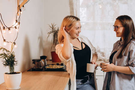 Couple of women drink coffee in the kitchen, happy laughing people. Selective focus.