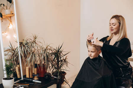 Eight-year-old blonde boy at the barbershop. A hairdresser cuts a haircut at a home beauty salon. Selective focus.