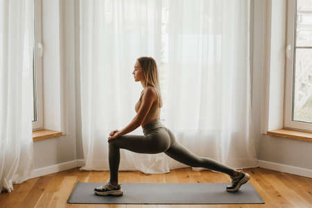 A young woman of European appearance practices yoga by the window. Sports at home. Self-isolation, online training.