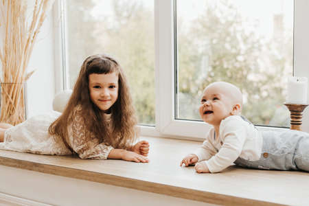 Little girl and toddler boy on a wooden windowsill. Beautiful children are playing. Family concept. Selective focus