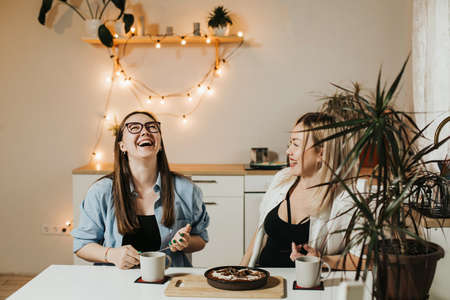Couple of ordinary women eating cake in the kitchen, happy laughing people at home.