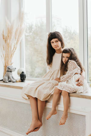 Two sisters sit on a windowsill in a beautiful Scandinavian interior. Lovely little girls. Portrait of two dark-haired children.