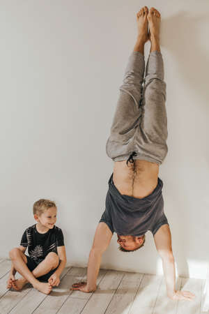 father and son go in for sports at home. The man is standing in a handstand. The boy sits and smiles. parenting, set an example. Health, sports concept.